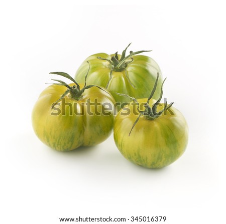 Trio of fresh ripe whole green tiger tomatoes in different sizes on a white background, composite view