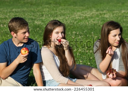 Trio of happy Caucasian teenagers eating fruit outdoors - stock photo