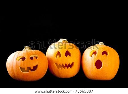 Trio of Jack-o-lanterns on black - stock photo