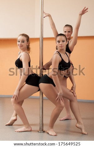 Trio of pretty young dancers posing with pylon