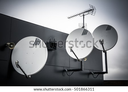 Trio of satellite dishes attached to high wall on building