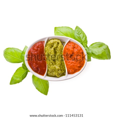 trio of sauces - pepper sauce, tomato, basil - dishes for sauces with three different kinds of sauces, a branch of basil isolated on white background - stock photo
