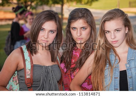 Trio of tough stylish teenage female students hanging out - stock photo