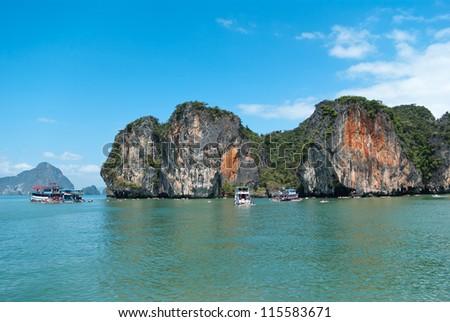 Trip boats by the tropical island in Andaman sea near Phuket, Thailand - stock photo