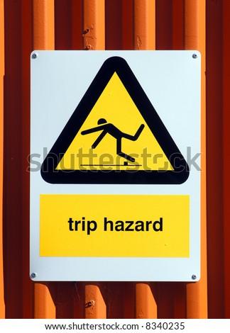 Trip Hazard sign on an orange tin wall - stock photo