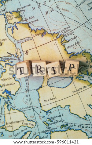 Trip word made from wooden letter blocks on a vintage map. Travel, holiday concept