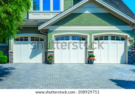 Triple doors garage with wide long driveway. - stock photo