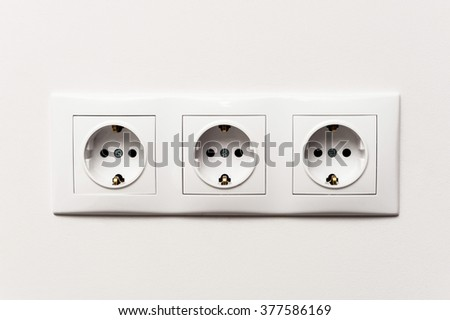 Triple electrical socket on white wall with black pattern - stock photo