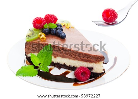 Triple layer, chocolate cheesecake served on a chocolate drizzled plate and garnished with raspberries, blueberries, kiwi, and fresh lemon balm.  Delicate citrus curls add a touch of elegance. - stock photo