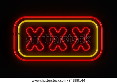 Triple X neon sign illuminated over dark background - stock photo