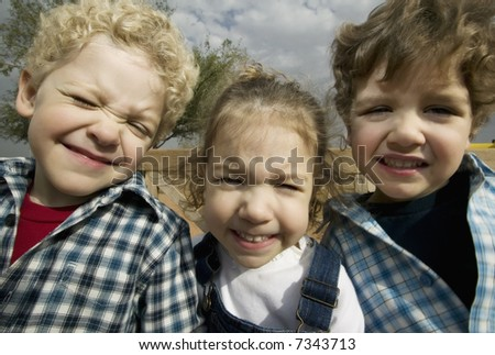 Triplets make faces in a wide angle portrait - stock photo