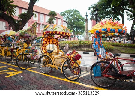 Trishaw decorated with colorful flowers waiting for customer in Malacca city that designated UNESCO world heritage site, Malaysia. Select focus at Center trishaw