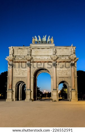 Triumphal Arch (Arc de Triomphe du Carrousel) at night in Tuileries gardens in Paris. Monument was built between 1806 - 1808 to commemorate Napoleon's military victories. France.