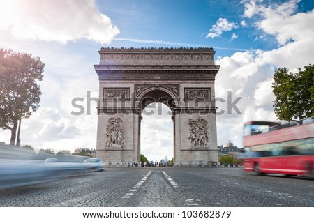 Triumphal arch. Blue sky and white clouds in background. Blurred cars and red tourist bus in foreground. Paris, France, Europe. - stock photo