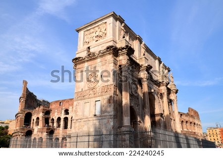 Triumphal Arch of Constantine and Colosseum in Rome against blue sky, Italy - stock photo