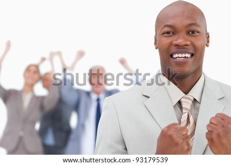 Triumphant businessman with cheering team behind him against a white background - stock photo