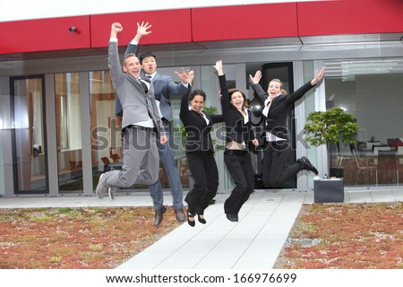 Triumphant multiethnic business team of diverse young people cheering and celebrating jumping in the air as they celebrate their success outside their office building - stock photo