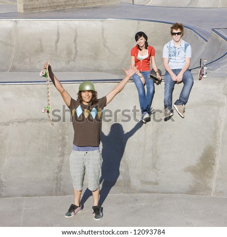 Triumphant skateboarder gestures infront of his friends - stock photo