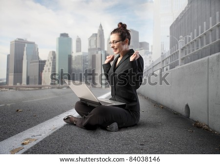 Triumphing businesswoman sitting on a city street and using a laptop - stock photo