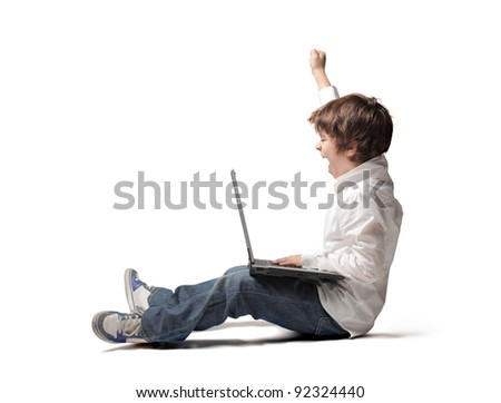 Triumphing child with a laptop on his knees - stock photo