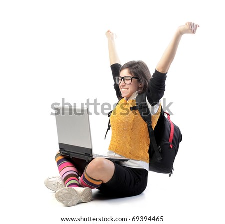 Triumphing young student in front of a laptop
