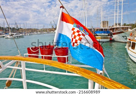 TROGIR, CROATIA - AUGUST 16, 2014. View of Trogir harbor and its medieval castle from the stern of a cruise ship at the quayside with the Croatian flag