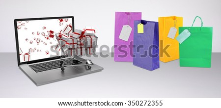 Trolley full of gifts on laptop against grey background