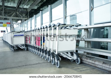 Trolleys luggage in a raw in airport. - stock photo