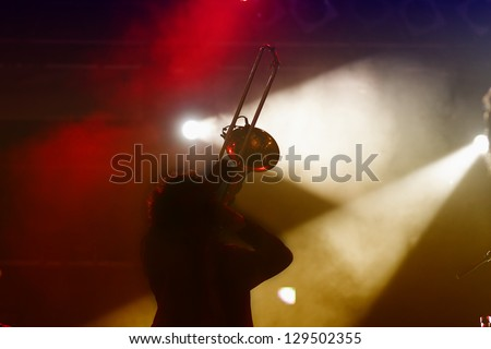 Trombone player silhouette on stage and abstract light - stock photo