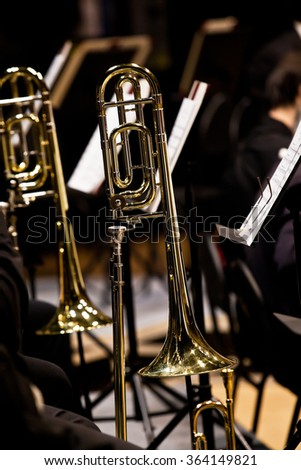 Trombones on stage in Symphony orchestra in dark colors - stock photo