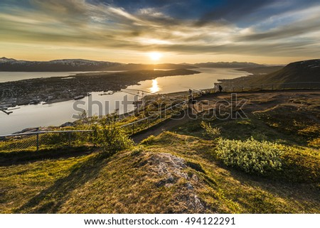 Tromso city in Tromsoya Island as seen from Mount Storsteinen under the Midnight Sun in Norway.