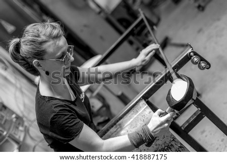 TROMSO, NORWAY - FEBRUARY 16, 2016: Girl is hand-crafting melted glass at a workshop in a glass factory, in black and white - stock photo