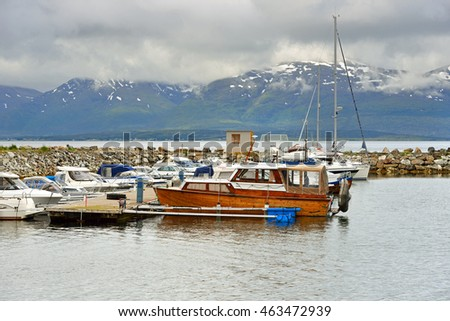 TROMSO, NORWAY - JUNE 15, 2016:Tromso is city and municipality in Troms county, Norway. Boats and yachts at mooring on a background of snow-capped mountains