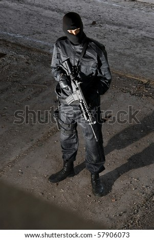 Trooper in black camouflage holding a gun - stock photo