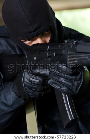 Trooper in black mask targeting with a gun - stock photo