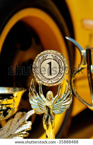 Trophies for winner and yellow wheel of racing car background - stock photo
