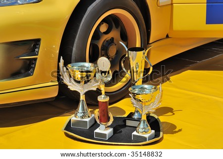 Trophies near a wheel of a yellow racing car - stock photo