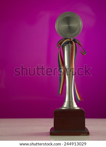 Trophy against the pink glass background - stock photo