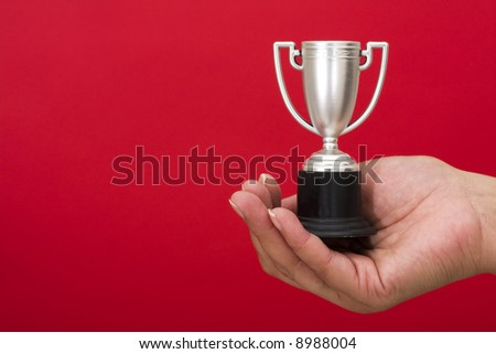 Trophy in hand on red background with copy space - stock photo