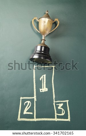 trophy on the blackboard with drawing podium 1,2,3 - stock photo
