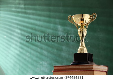 trophy on top stack of book in front of black board - stock photo