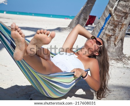 Tropic lounging. View of nice woman in hammock in tropical environment. Summer luxury vacation - stock photo