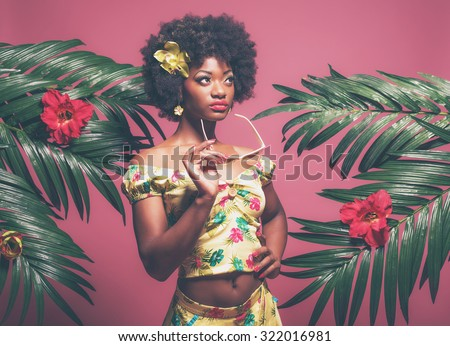Tropical Afro American Pin-up Holding Sunglasses. Against Pink Background. - stock photo