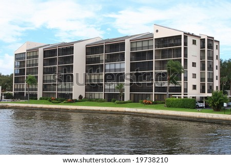 Tropical apartment building over looking a waterway out to the ocean - stock photo