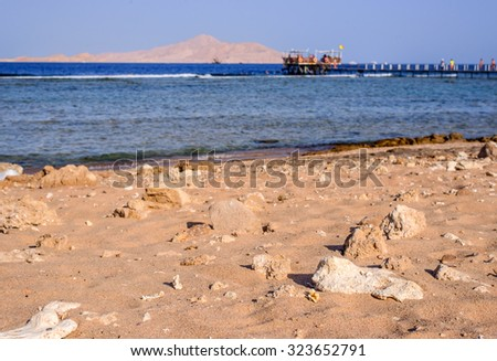 Tropical bay with a wooden jetty or pier leading out over the shallow tidal water to the edge of the channel and deeper water with wooden huts for tourists to enjoy their summer vacation - stock photo