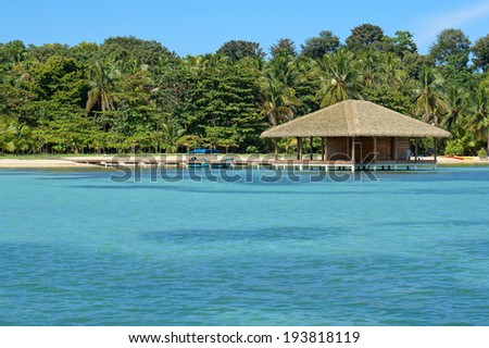 Tropical beach and bungalow over water with exotic roofing made of synthetic palm leaves - stock photo