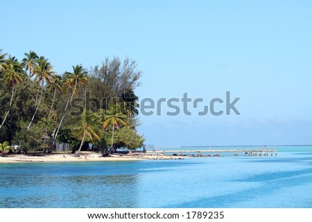 Tropical beach and pier on the lagoon - stock photo
