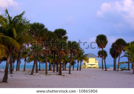 Tropical beach at dusk with palm trees and yellow lifeguard hut.