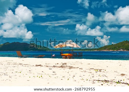 Tropical beach at Seychelles with picnic table and chairs - stock photo