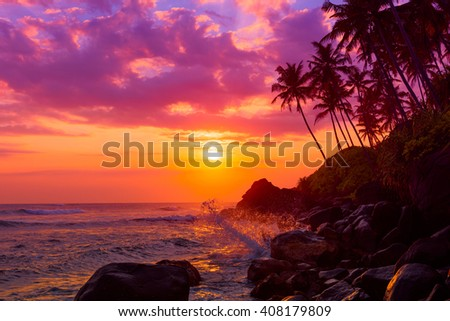 Tropical beach at sunset with palm trees silhouettes and shiny waves splashe - stock photo